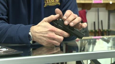 assault rifles and handguns in a gun shop on december 4, 2015. - 銃器店点の映像素材/bロール