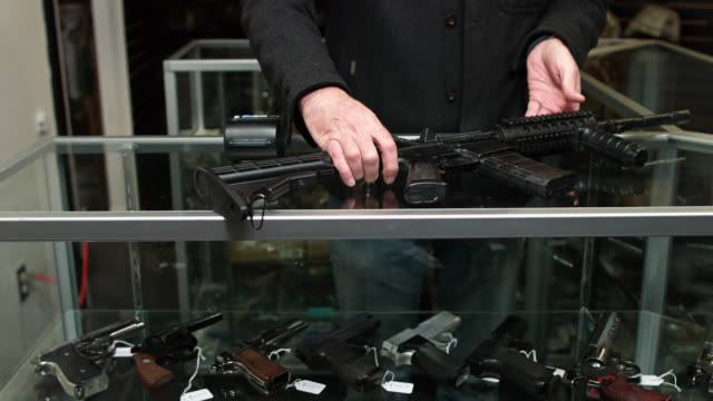 assault weapon being placed on gun display case - weaponry stock videos & royalty-free footage