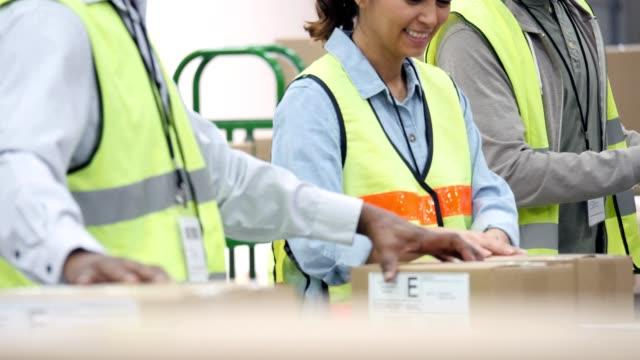 流通倉庫の従業員の組立ラインは、配送用のパッケージを準備します。
