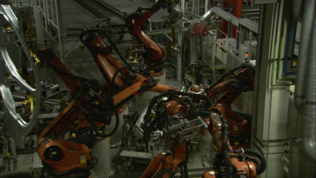 assembly line robots rotate and work on different car parts in a bmw plant. - bmw stock videos & royalty-free footage