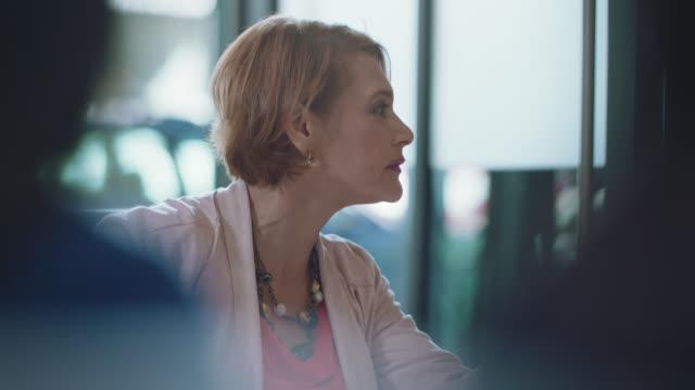 vídeos de stock e filmes b-roll de assertive businesswoman converses with a fellow businesswoman during an important meeting - liderança