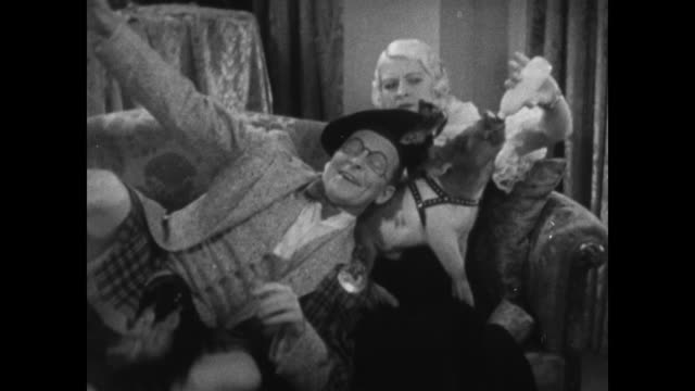 1934 assertive man places pet pig in surprised woman's lap before lying down next to her - 1934 stock videos & royalty-free footage
