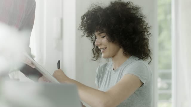Assistant brings document for signing to businesswoman to her office