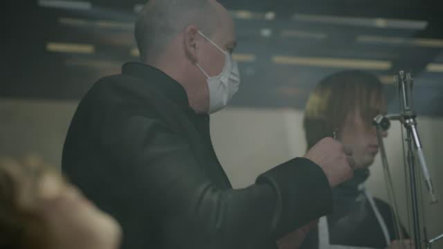 vídeos de stock, filmes e b-roll de assistant giving syringe to evil dentist injecting patient / cedar hills, utah, united states - evil
