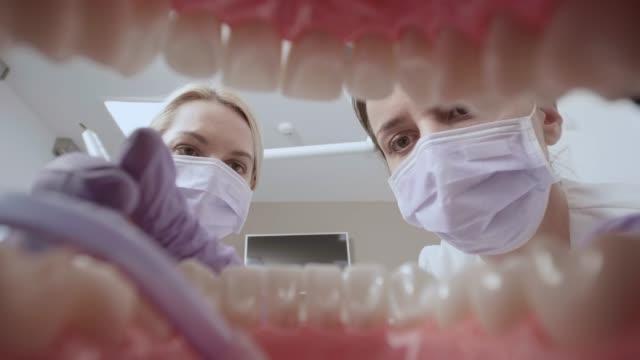 vídeos de stock, filmes e b-roll de pov assistente colocar uma mangueira de sucção na boca do paciente antes de dentista começa a trabalhar no dente - dentista