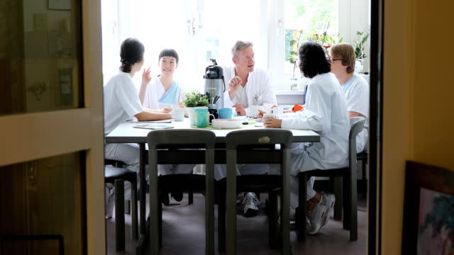 Assistants and doctors discussing at table
