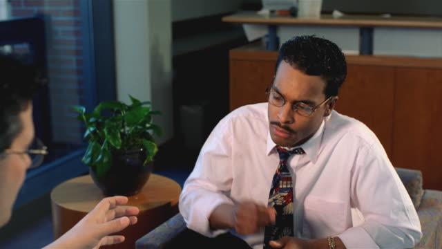 associates meeting in office, closeup of african american businessman - skjorta och slips bildbanksvideor och videomaterial från bakom kulisserna