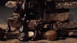 Assorted chocolate and nuts covered with chocolate topping. Close-up sliding shot