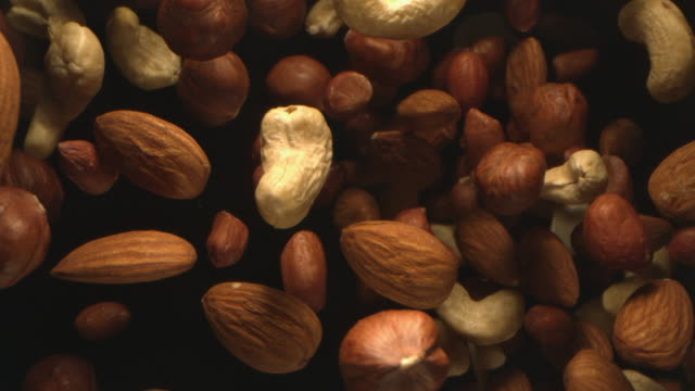 assorted nuts flying in the air in a free fall in slow motion on black background at 1000 fps 4k - nutshell stock videos & royalty-free footage