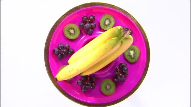 vídeos de stock, filmes e b-roll de ws zi cu ha assortment of fruit rotating against white background / orem, utah, usa - enfoque de objeto sobre a mesa