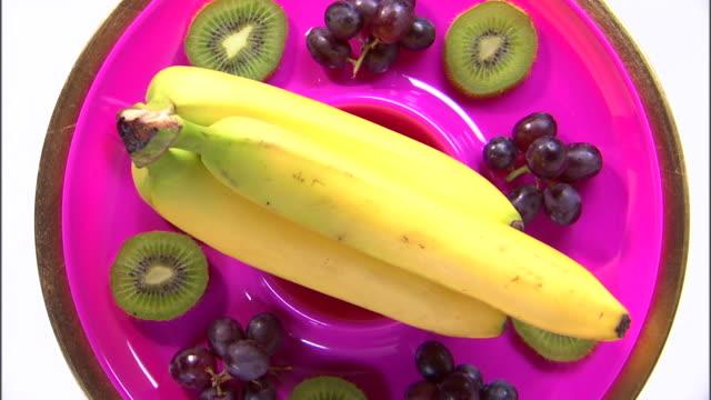 vídeos de stock, filmes e b-roll de cu zi ha assortment of fruit rotating against white background / orem, utah, usa - enfoque de objeto sobre a mesa