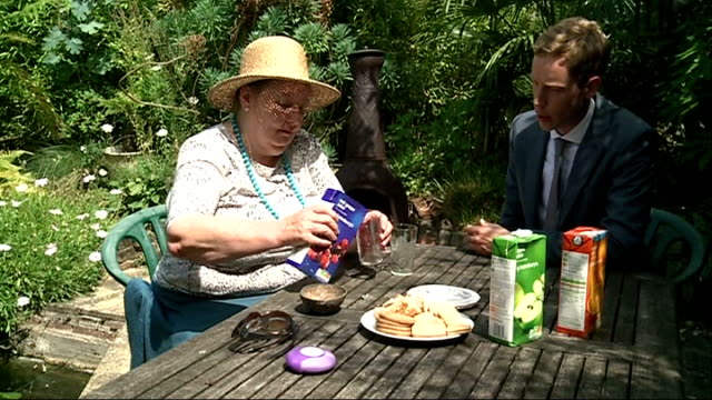 Asthma sufferers missing essential annual checkups Hand picking up inhaler Joanna Day and reporter sitting at table in garden