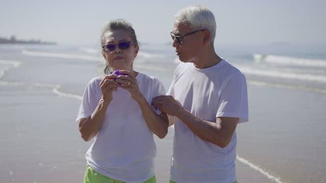 asthmatic senior gray hair woman using a violet inhaler with feeling care, of senior man, husband while walking in morning along the beach at summer day, vacation weekend, concept of retirement people with asthmatic illness - running shorts stock videos & royalty-free footage