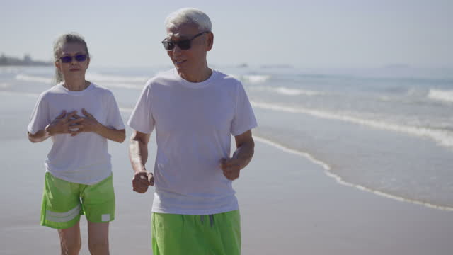 asthmatic senior gray hair woman using a violet inhaler with feeling care, of senior man, husband while jogging, running, exercising in morning along the beach at summer day, vacation weekend, concept of retirement people with asthmatic illness - running shorts stock videos & royalty-free footage