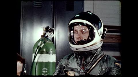 vidéos et rushes de astronaut alan shepard wearing spacesuit and preparing for project mercury iii mission / technician testing spacesuit speaker system on july 28, 1961... - 1961