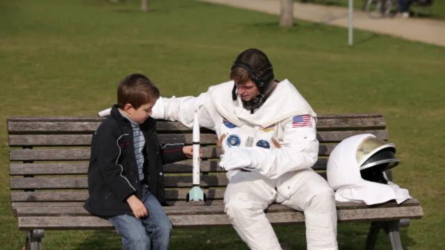 vídeos y material grabado en eventos de stock de ms astronaut and boy (6-7) sitting on park bench playing with toy rocket / berlin, germany - astronauta