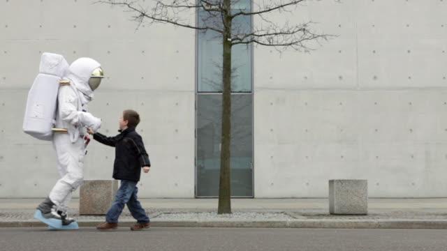 WS Astronaut and boy (6-7) walking down street / Berlin, Germany