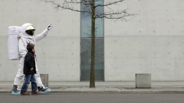 WS Astronaut and boy (6-7) walking down street holding hands / Berlin, Germany