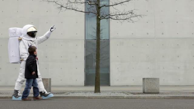 vídeos y material grabado en eventos de stock de ws astronaut and boy (6-7) walking down street holding hands / berlin, germany - astronauta