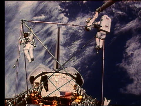 astronaut building metal frame in open shuttle bay - 宇宙服点の映像素材/bロール