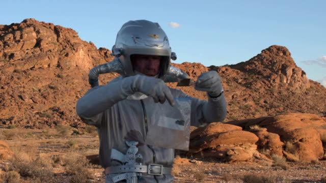 vídeos de stock e filmes b-roll de astronaut collecting soil samples - porta amostra