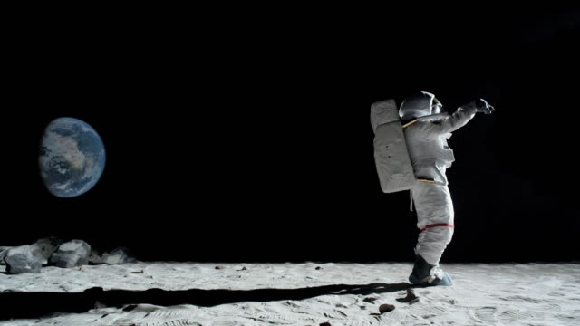 ws slo mo astronaut doing the moonwalk on the moon surface / berlin, germany - humor stock-videos und b-roll-filmmaterial