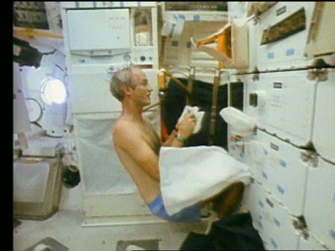 Astronaut Don Williams shaving on Space Shuttle Atlantis