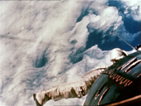 astronaut ed white makes the first spacewalk for the us during the gemini 4 mission / view from space capsule of astronaut in spacesuit floating in... - gemini 4 stock videos and b-roll footage