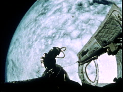 astronaut edward white communicating with control and being instructed to return to the spacecraft as he floats in space above earth during gemini iv... - gemini 4 stock videos and b-roll footage