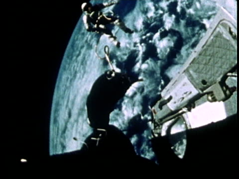vídeos de stock, filmes e b-roll de astronaut edward white communicating with control as he floats in space above earth during gemini iv mission spacewalk - 1965