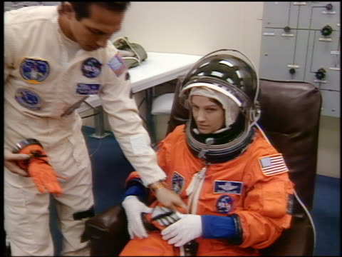 Astronaut Eileen Collins waving as man helps her into spacesuit before launch / STS84