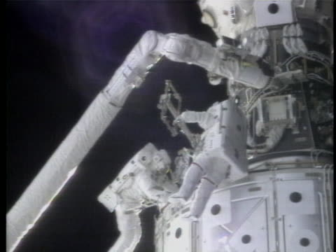 of astronaut ellen ochoa in a red shirt seen in the international space station moving items then it flashes to a two astronauts seen working on the... - all shirts stock-videos und b-roll-filmmaterial