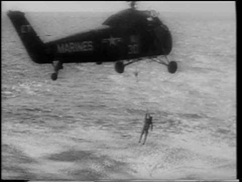 aerial astronaut gus grissom being lifted from ocean to helicopter after splashdown - splashdown stock videos and b-roll footage