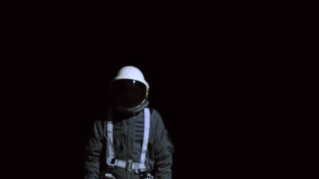 astronaut in space suit walking towards camera - luftfahrtindustrie stock-videos und b-roll-filmmaterial