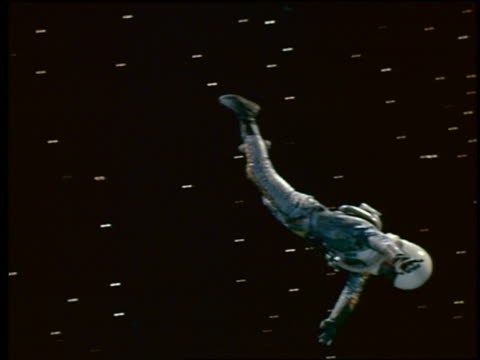 Astronaut in spacesuit floating upside down thru space