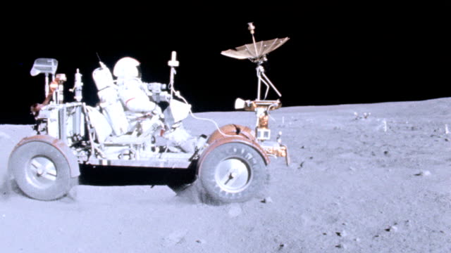 astronaut john young driving lunar rover vehicle on moon surface during apollo 16 mission / rover kicks up dust as it drives around in circles. - moon stock videos & royalty-free footage