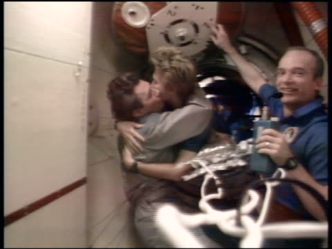 Astronaut Kondakova hugging kissing cosmonaut Tsibiliev in MIR as Precourt looks on / STS84