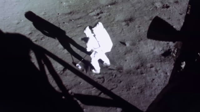 astronaut neil armstrong is moving out into the sunlight to scoop up the very first bag of rocks and soil that we humans would pick up on another... - nasa video stock e b–roll