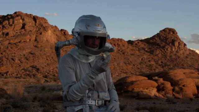 vídeos de stock, filmes e b-roll de astronauta em um planeta estranho descobre uma estranha bola de cristal - amostra científica