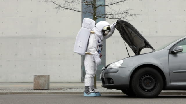 WS Astronaut on city street having car trouble / Berlin, Germany