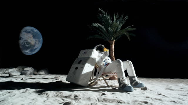 ws slo mo astronaut on moon sitting in beach chair, toasting his cocktail / berlin, germany - 宇宙飛行士点の映像素材/bロール