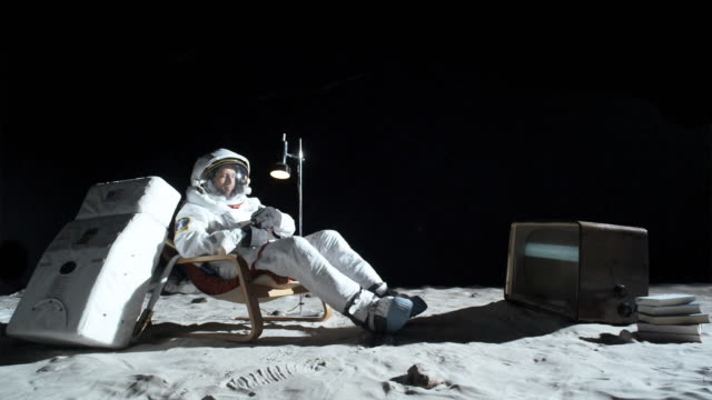 ws slo mo astronaut on moon sitting in easy chair, watching tv and drinking beer / berlin, germany - astronaut stock videos & royalty-free footage