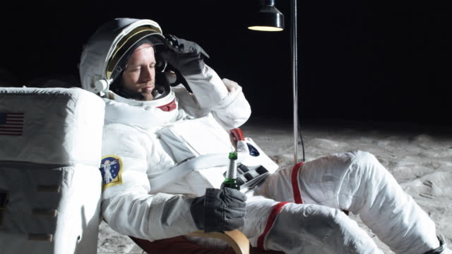 ms slo mo astronaut on moon sitting in reclining chair while drinking beer / berlin, germany - helm stock-videos und b-roll-filmmaterial