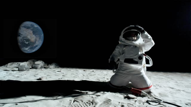 ws slo mo astronaut on moon unplugging cord from extension cord / berlin, germany - auseinander stock-videos und b-roll-filmmaterial