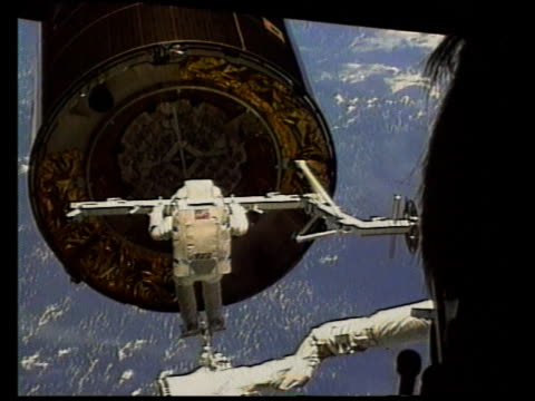 astronaut on shuttle arm reaching for satellite in space - 宇宙服点の映像素材/bロール