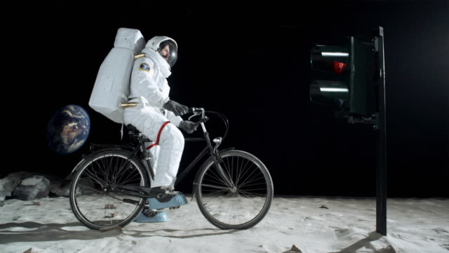 ws slo mo astronaut on the moon riding bicycle, stopping for red light and resuming his ride when the light turns green / berlin, germany - helm stock-videos und b-roll-filmmaterial