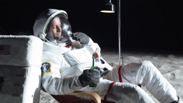 ms slo mo astronaut on the moon sitting in easy chair, drinking beer / berlin, germany - 宇宙飛行士点の映像素材/bロール