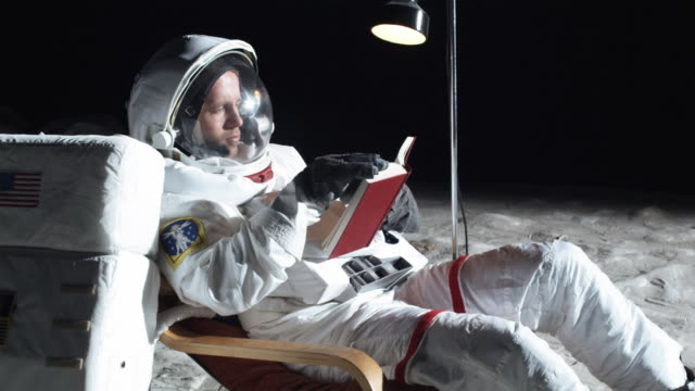 MS SLO MO Astronaut on the moon sitting in reclining chair, reading book / Berlin, Germany
