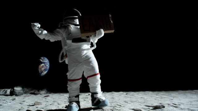 WS SLO MO Astronaut on the moon unsuccessfully hitchhiking with an EARTH sign / Berlin, Germany