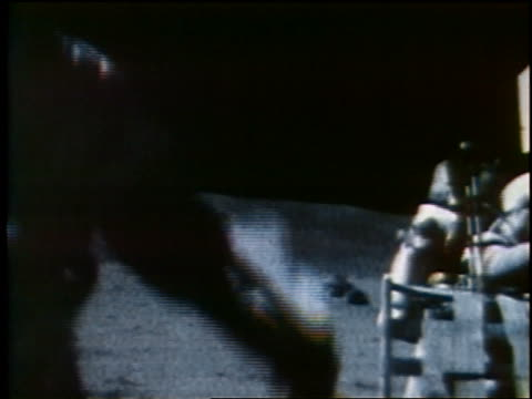 1972 astronaut passing camera with another in background on Moon / Apollo 16